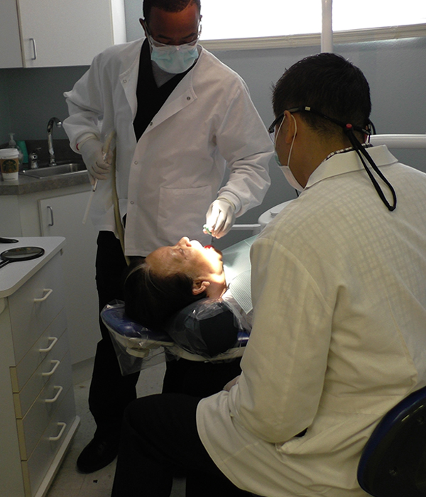 Dr. Fu and dental assitant with patient